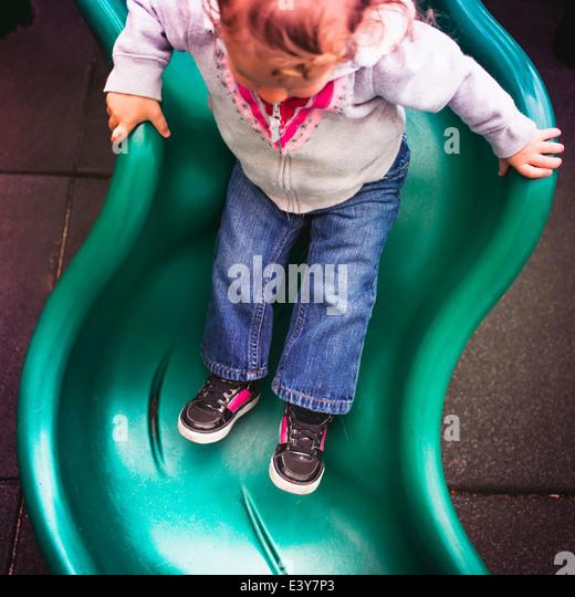 Toddler going down slide in playground - Stock-Bilder