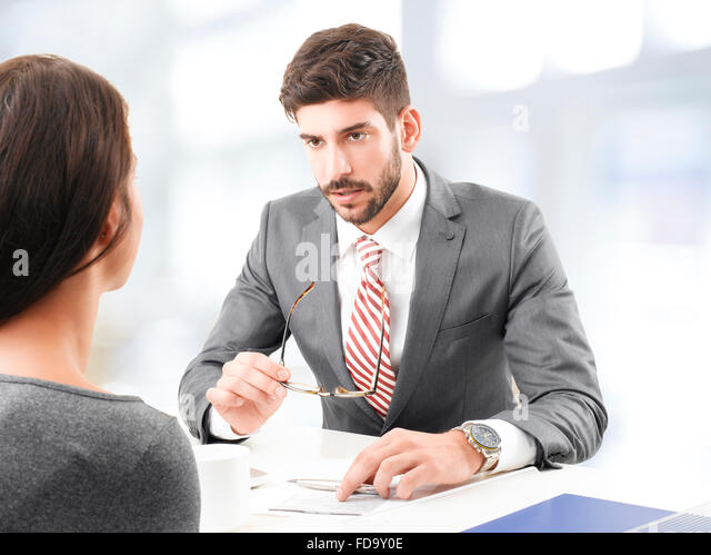 Portrait of confident investment adviser giving advise for busy business woman, while sitting at office. - Stock-Bilder