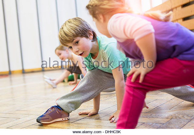 Children stretching, legs bent, leaning forwards - Stock-Bilder