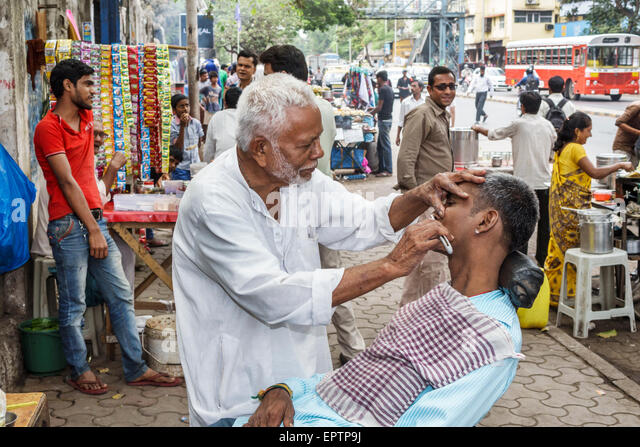 India Asian Mumbai Dharavi Senapati Bapat Marg man barber shaving customer sidewalk street single blade razor job - Stock Image