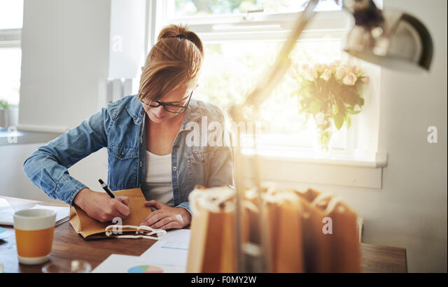 Young Woman Writing Some Notes on Paper Gift Bag on Top of the Wooden Table inside the House Against the Glass Window. - Stock Image
