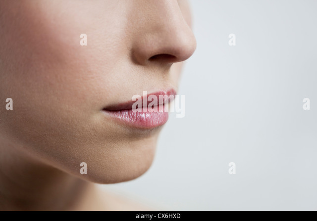 Close up of a young womans mouth, closed - Stock Image