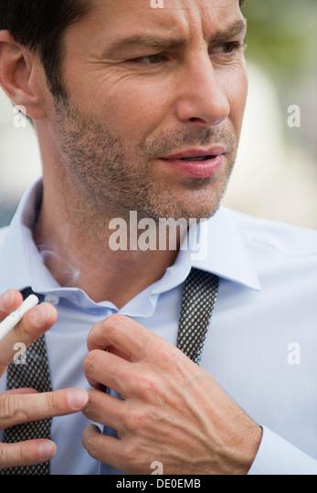 Businessman putting on necktie - Stock-Bilder