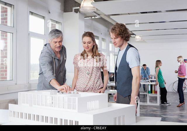 Germany, Bavaria, Munich, Man explaining architectural model to colleagues - Stock-Bilder