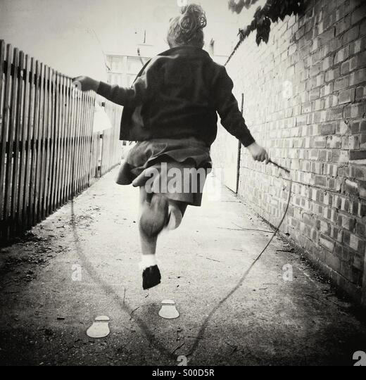 Young girl skipping against the one way system of the footprints. Rebel. - Stock Image
