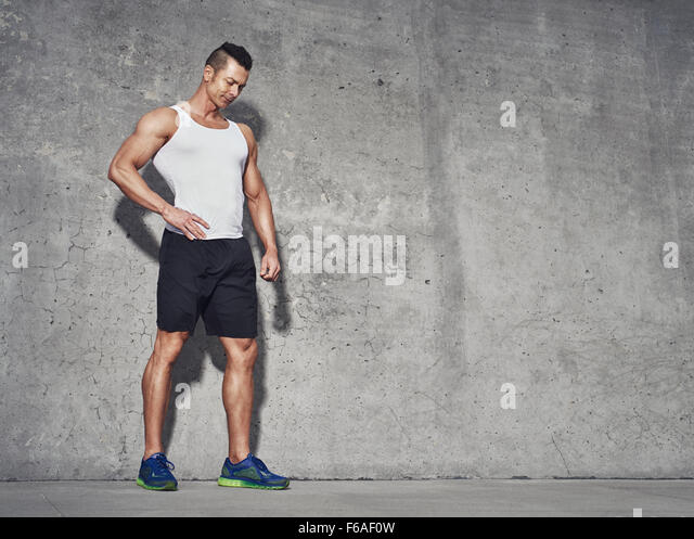 Male fitness model in white tank top relaxing after workout. Grey background with room for text, Copy space - Stock Image
