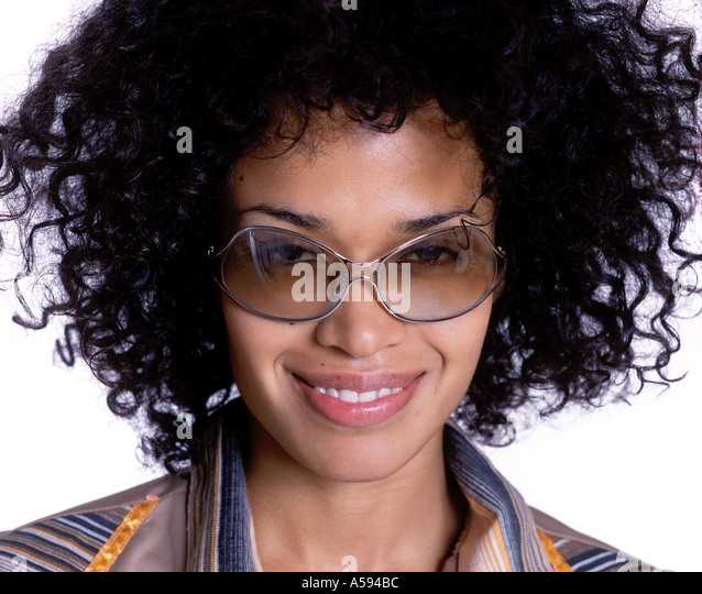 Young Woman With Curly Hair And Sunglasses Smiling - Stock Image