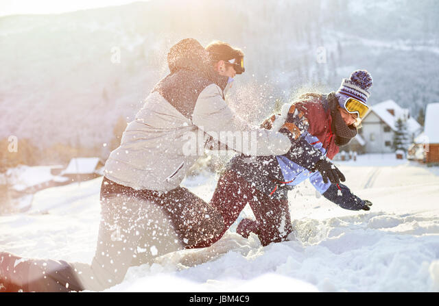Playful couple enjoying snowball fight in snowy field - Stock-Bilder