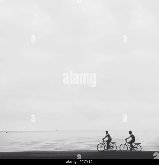 Men Riding Bicycle On Beach Against Clear Sky - Stock Image