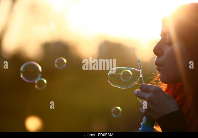 Netherlands, Amsterdam, Side view of young woman blowing bubbles - Stock Image