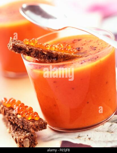 Creamed tomato soup with pepper and salmon eggs - Stock Image