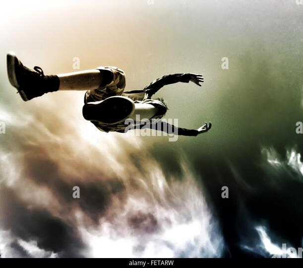 Directly Below Shot Of Boy Jumping Against Cloudy Sky - Stock Image