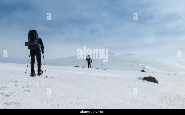 two men with heavy backpacks snowshoeing through a winter mountain landscape. Huldraheimen, Gausdal vestfjell, Norway - Stock Image