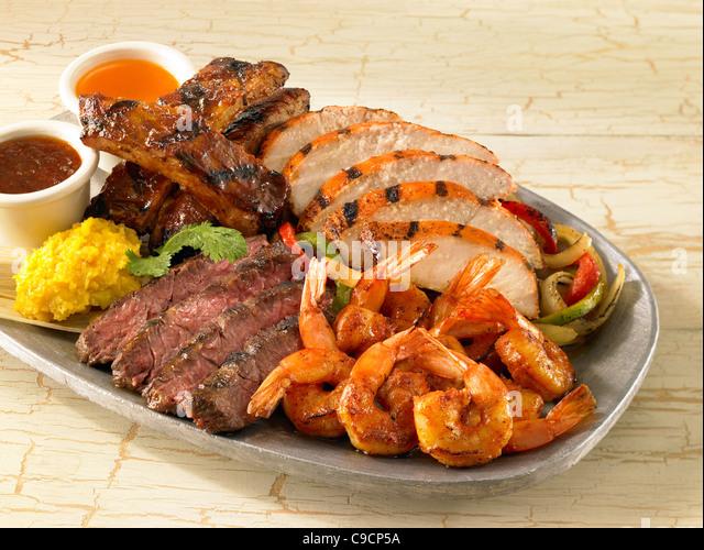 Shrimp, chicken, beef and pork rib fajitas served over vegetables - Stock Image