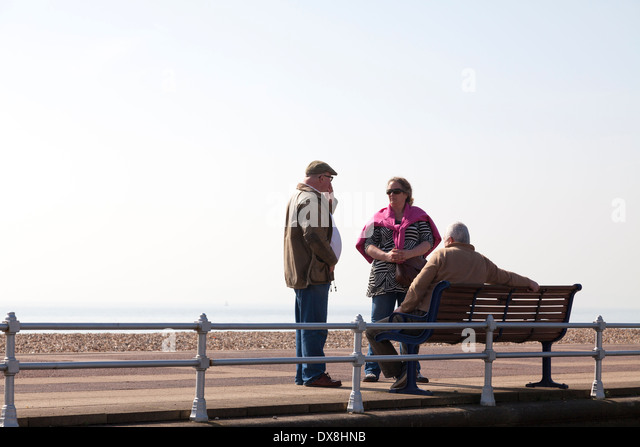 Middle aged group of three friends around bench on promenade. - Stock Image
