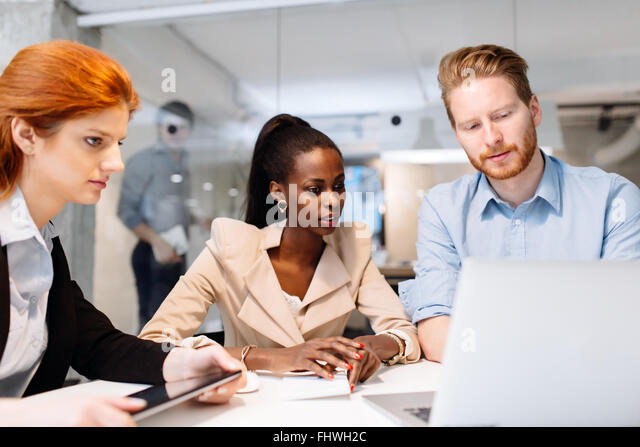 Group of business people sitting at desk and having a meeting about future strategy - Stock Image