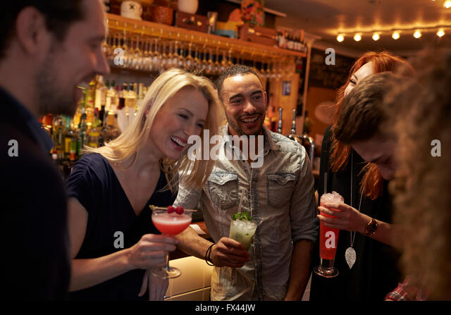 Group Of Friends Meeting For Evening Drinks In Cocktail Bar - Stock Image