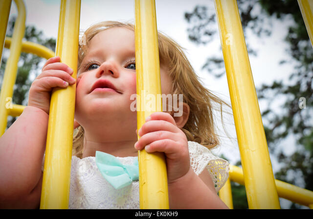 A small, blond toddler peeking through the bars of a jungle gym at a park playground. - Stock-Bilder