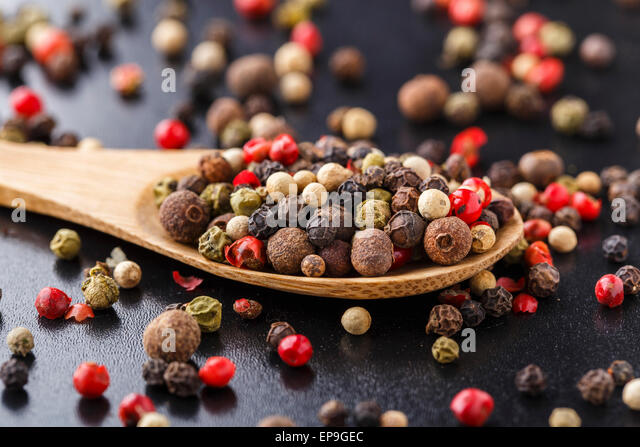 Mix of peppers on a wooden spoon - Stock Image