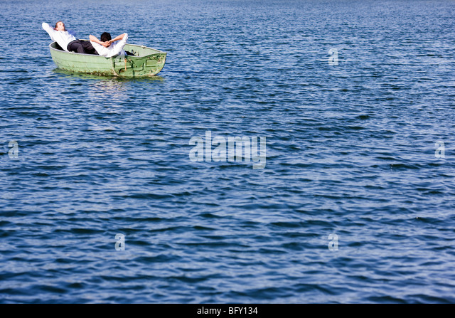 two businessmen relaxing in rowboat - Stock Image