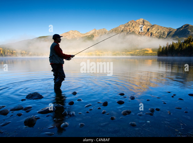 Middle age male fly fishing in Pyramid Lake, Jasper National Park, Alberta, Canada. - Stock Image