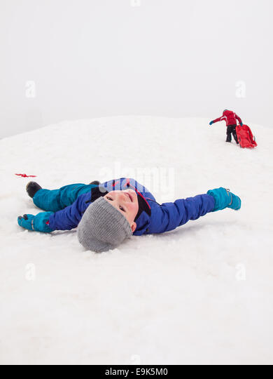 small boy lying smiling on snow at the bottom of a sledging hill - Stock Image