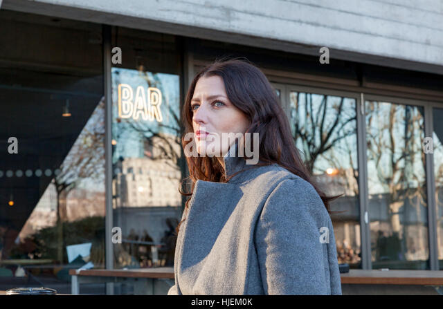 Attractive dark haired woman standing outside a bar - Stock Image