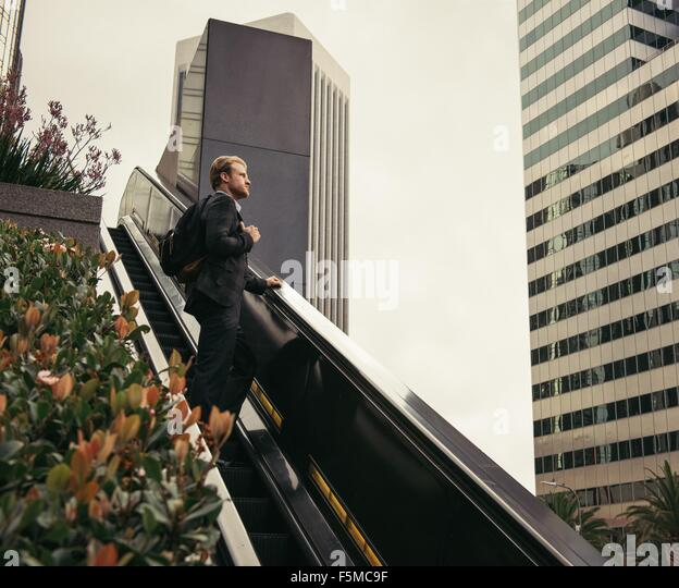 Businessman moving up escalator, Los Angeles, USA - Stock-Bilder