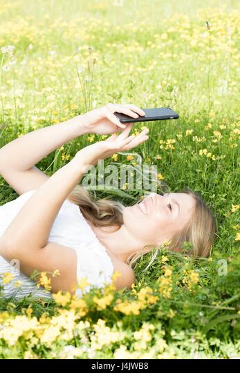 MODEL RELEASED. Young woman lying on grass with cell phone. - Stock-Bilder