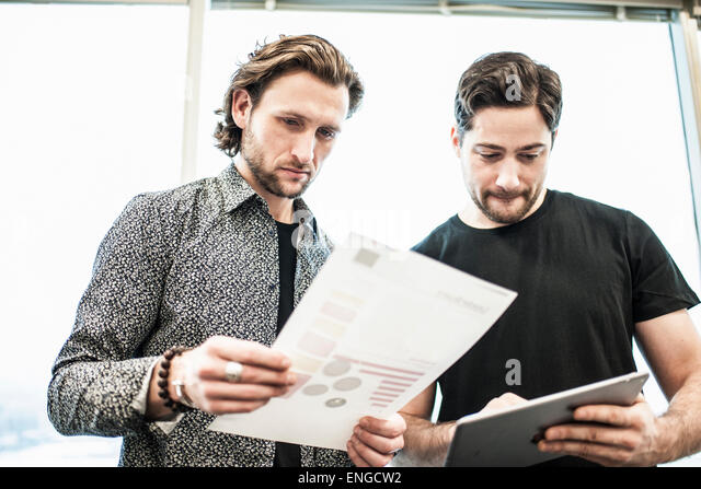 Two men standing in an office, looking at a page of printing, and referring to a digital tablet. - Stock Image