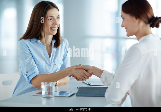 Personal manager greeting a woman at job interview - Stock Image
