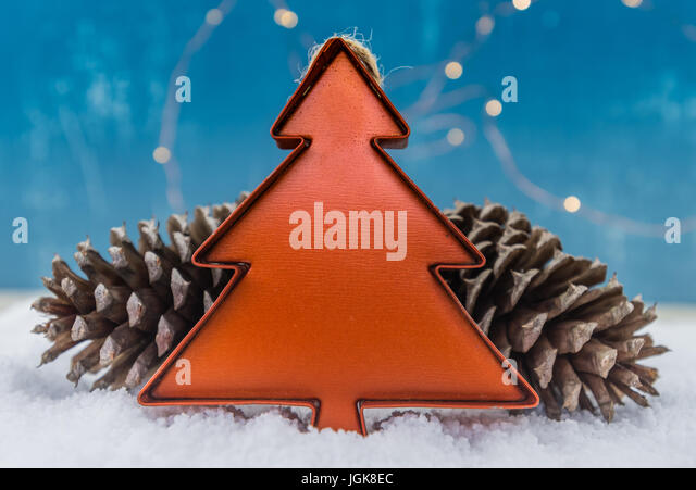 Tin Christmas Tree Ornament with Pine Cones over snow - Stock Image