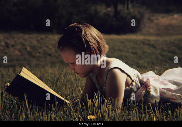 Girl lying on grass reading book - Stock Image