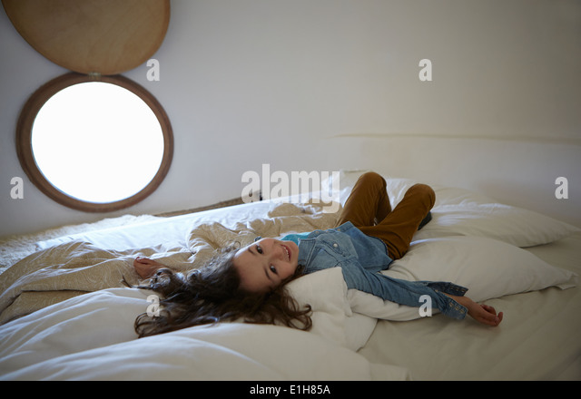 Candid portrait of girl lying on bed - Stock Image