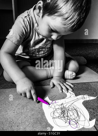 Little boy drawing on a small piece of paper - Stock-Bilder