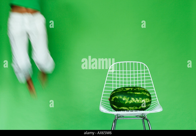 Young woman jumping by watermelon on chair, (blurred motion) - Stock Image