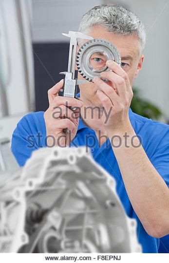 Engineer measuring gear wheel with vernier caliper - Stock Image