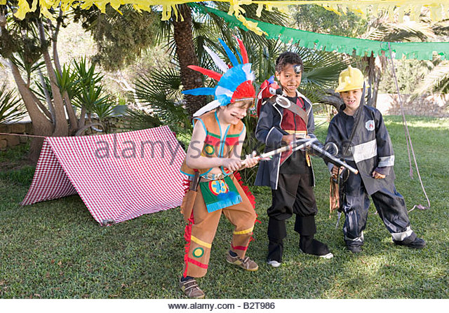 Boys in indian, pirate and fireman costumes - Stock Image