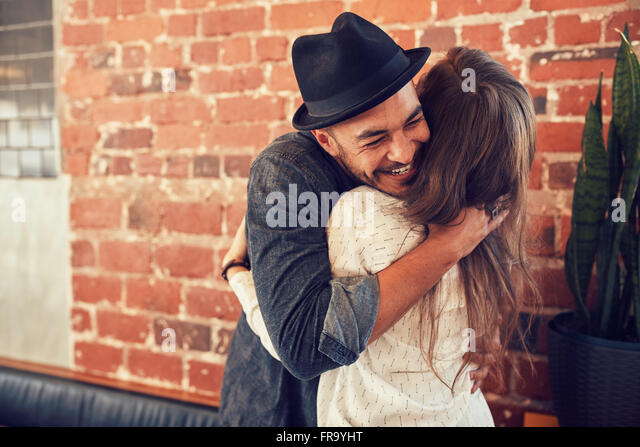 Portrait of young man embracing his girlfriend at cafe. Young man hugging a woman in a coffee shop. - Stock Image