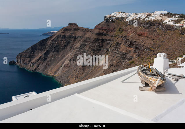 A small, weathered rowing boat used as a picturesque ornament on a flat white roof with the caldera cliffs in the - Stock Image