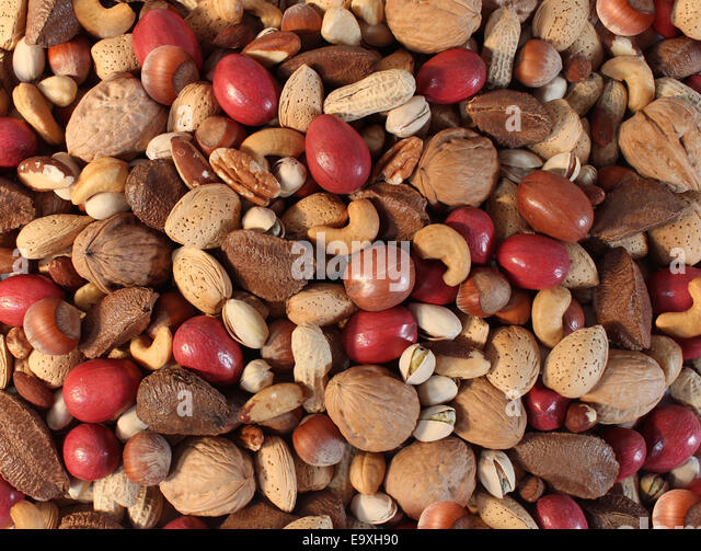Nuts background with a mixed assortment of seeds and pecan with walnut brazil nut peanut,hazelnut pistachio almond - Stock Image