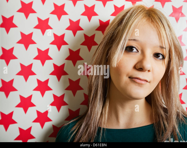 Close-up of beautiful young woman gainst red star shapes wallpaper - Stock Image