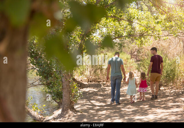 Rear view of male couple strolling with two daughters in park - Stock-Bilder