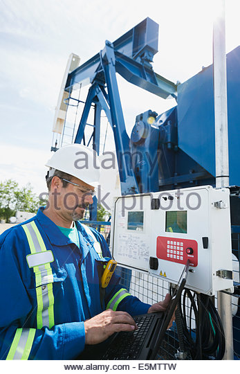 Male worker with laptop at oil well - Stock Image