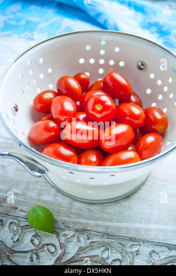 Grape Tomatoes in a White Strainer - Stock Image