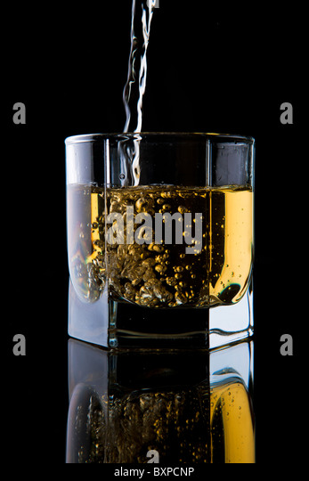 Glass of whisky on a black background. - Stock Image
