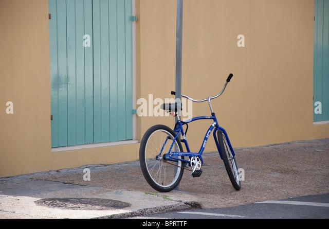 blue bicycle parked on sidewalk - Stock Image