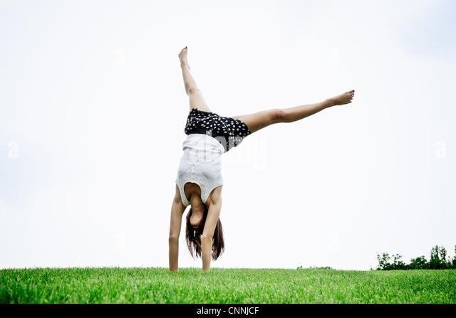 Woman doing cartwheel outdoors - Stock Image