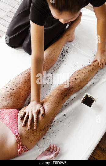 Woman Receiving Coffee Scrub at Indigo Pearl, Phuket, Thailand. A woman receives a coffee body scrub outdoors in - Stock Image