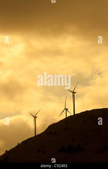 Silhouette view of wind generators on Pillar Mountain above Kodiak at sunset, Southwest Alaska, Spring - Stock Image